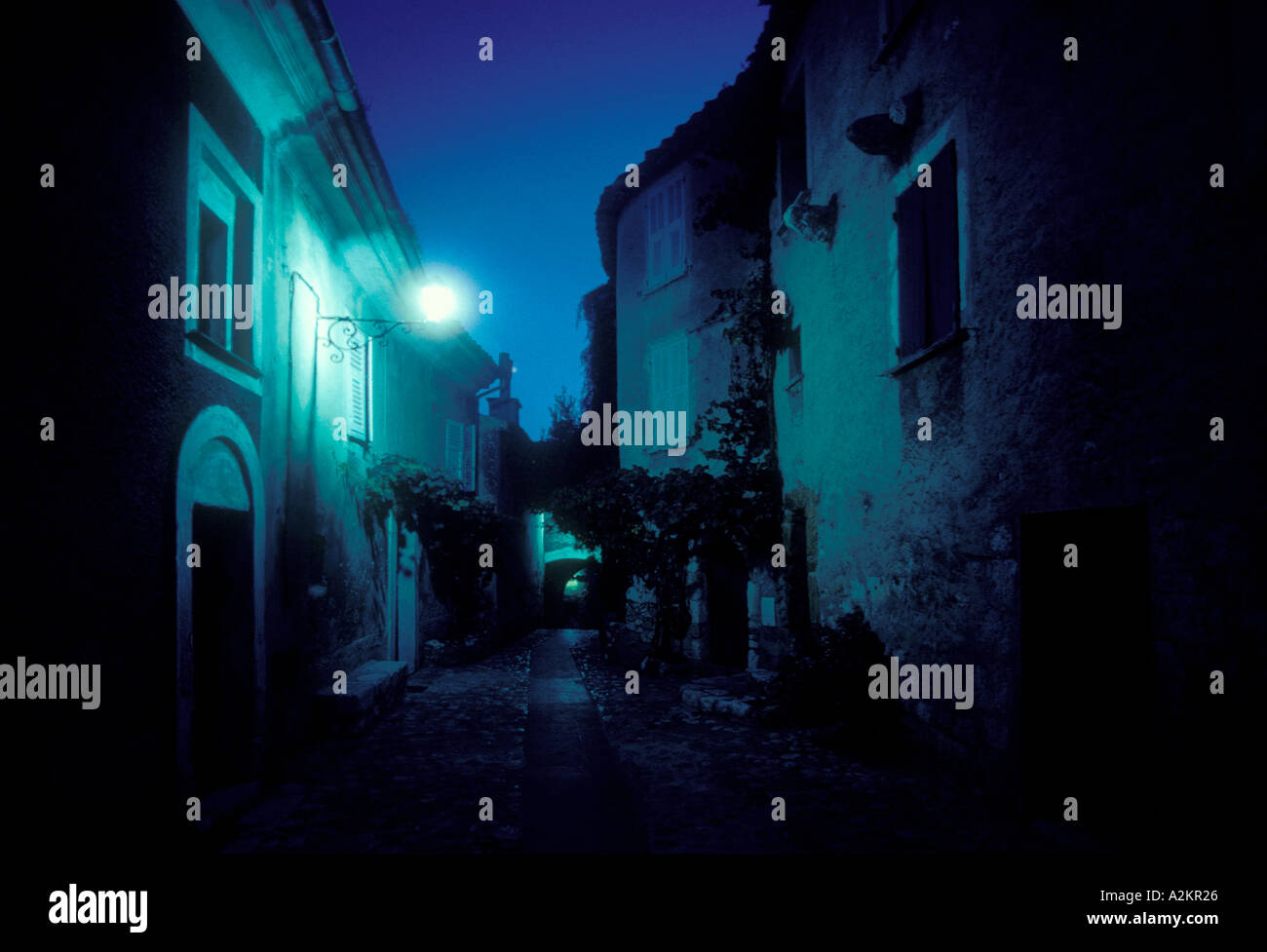 At dusk streetlight illuminates an alley in Eze a medieval walled city in the Cote D Azur on the French Riviera - Stock Image