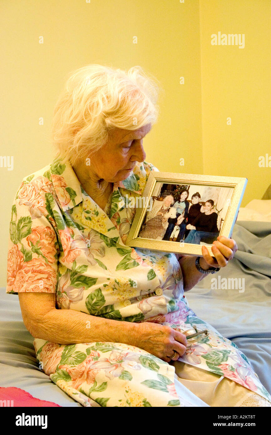 old lady sitting on edge of bed looking yearningly at framed family photo - Stock Image