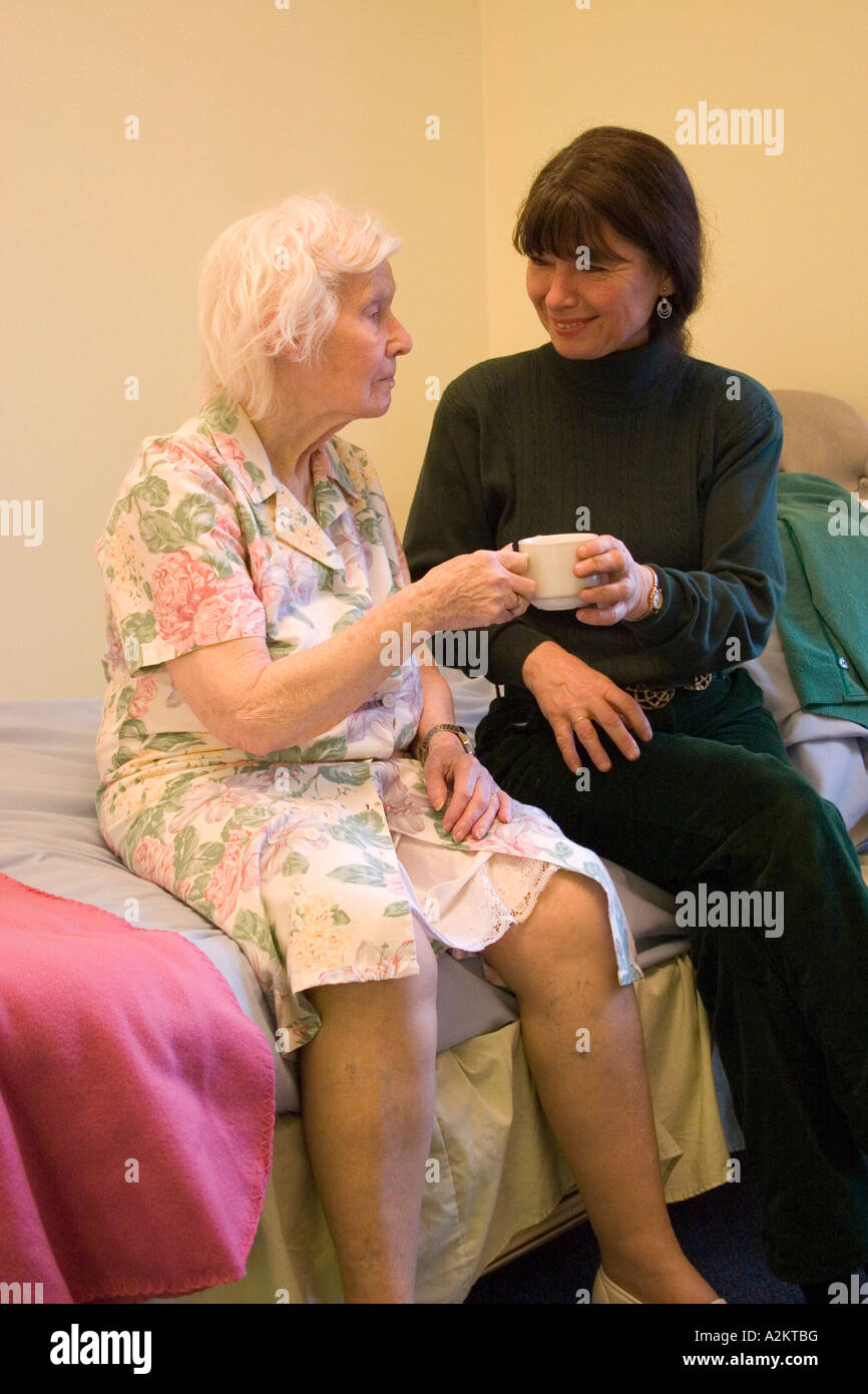 middle aged woman/daughter/care worker giving tea to old lady/her mother in nursing home - Stock Image