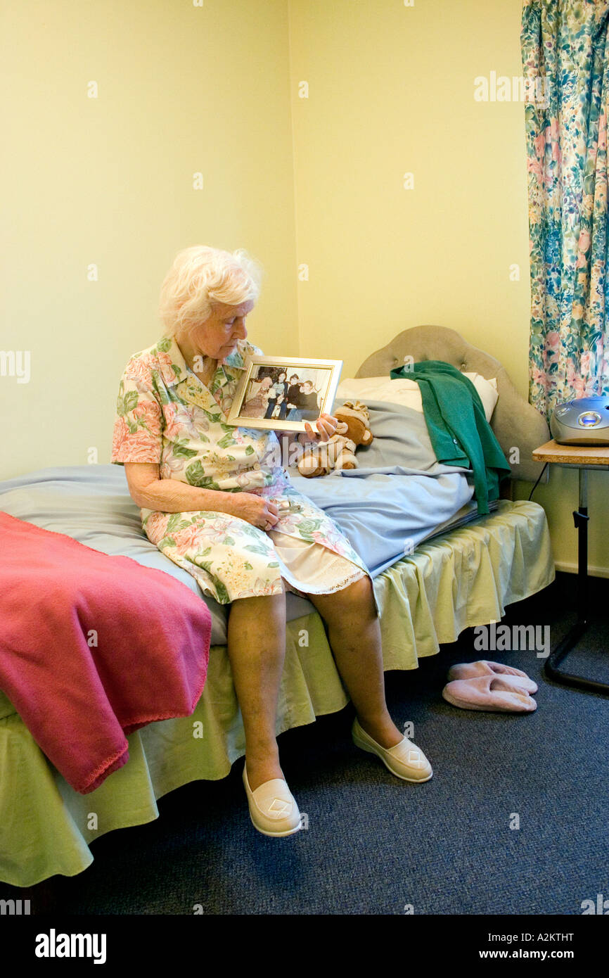 geriatric/old lady sitting on edge of bed in nursing home looking at family photo - Stock Image