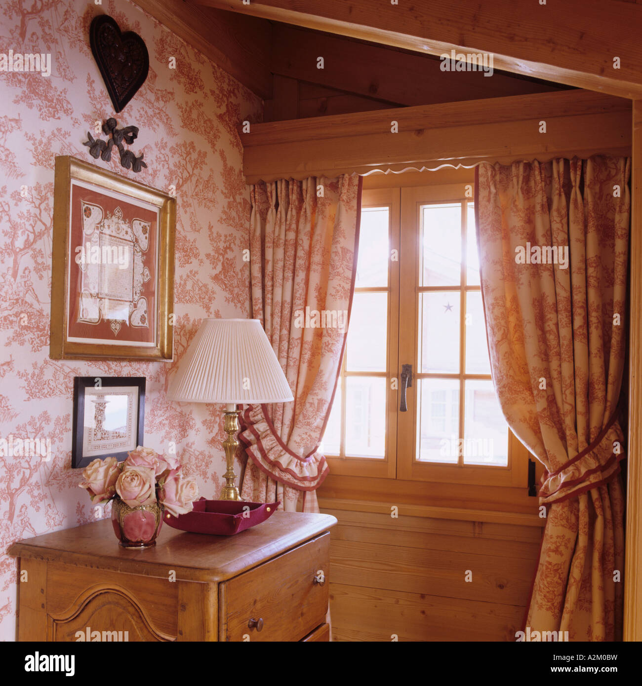 Window in room with matching curtains and wallpaper in a traditional chalet in Switzerland - Stock Image