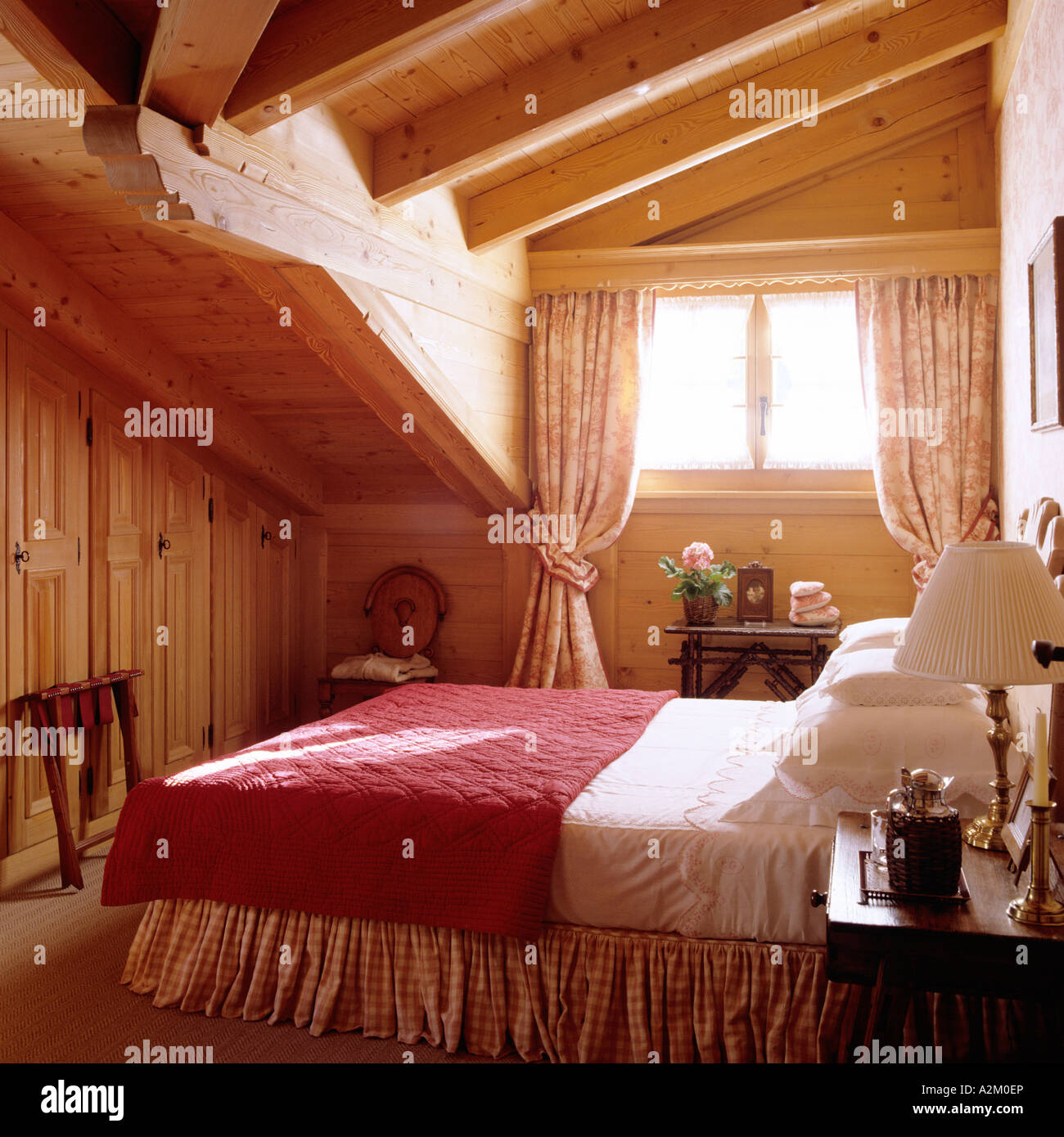 Bedroom with beamed ceiling in a traditional chalet in Switzerland Stock Photo