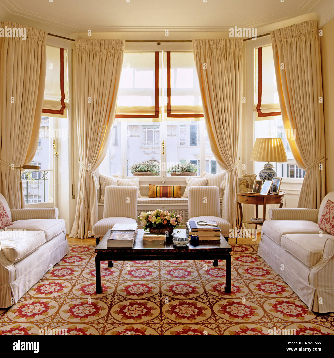 Large living room with three sofas, patterned carpet and bay windows - Stock Image