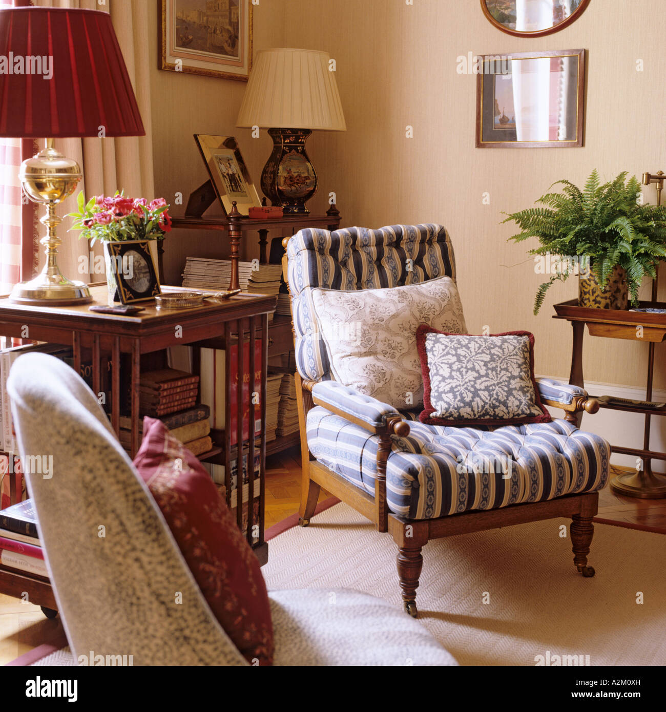 Upholstered armchair with cushions and lamps on shelf table - Stock Image
