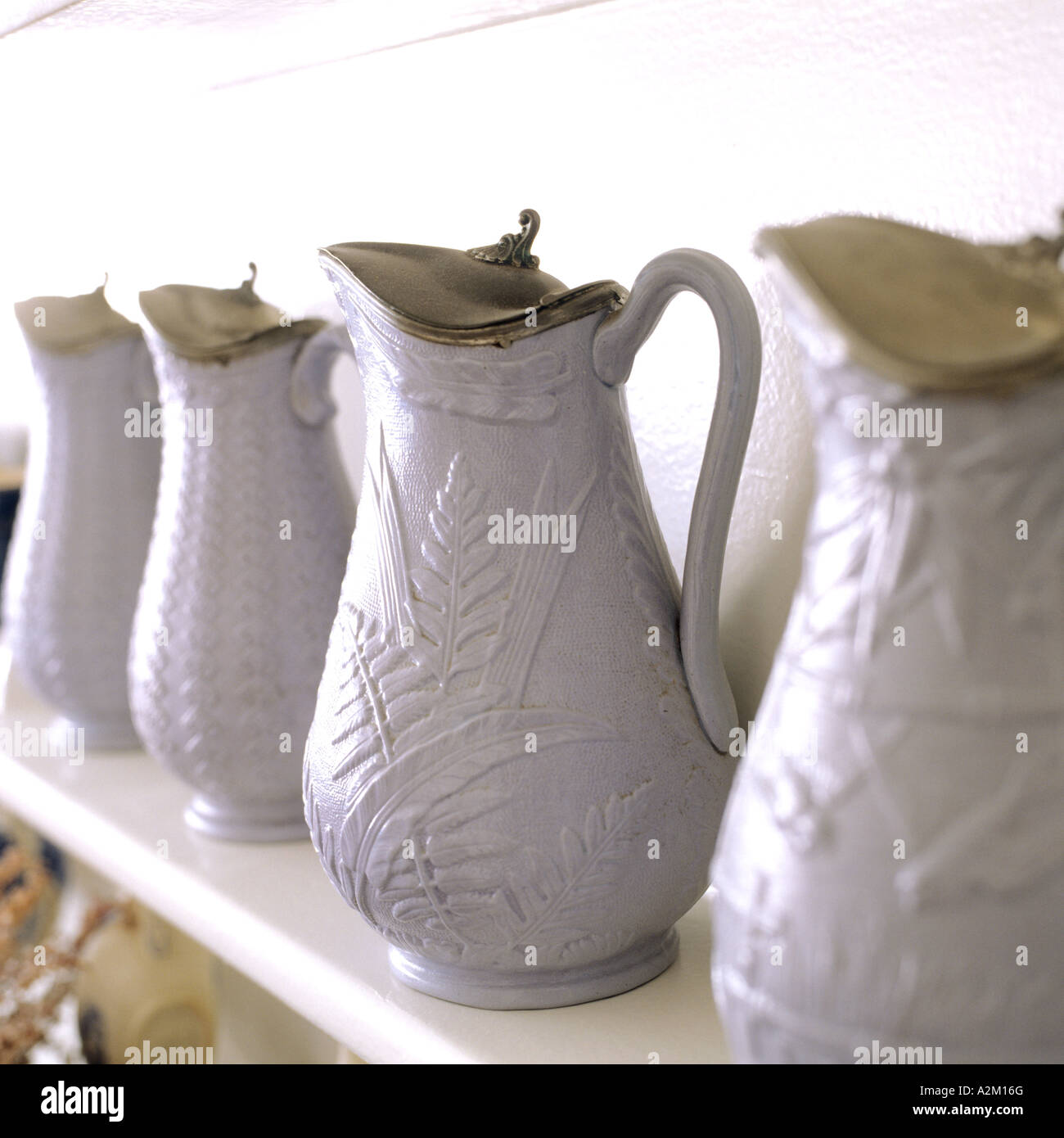collection of pale blue china jugs with silver lids on a shelf - Stock Image