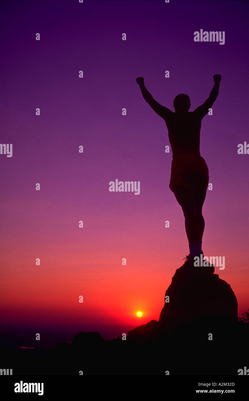 Silhouette of a young woman runner standing with her arms outstretched on top of a mountain peak with sunset in the background - Stock Image
