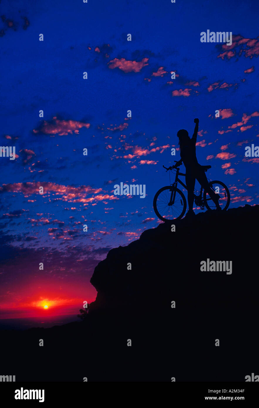 Silhouette of a young woman with a bicycle standing with her arm outstretched on top of a mountain peak - Stock Image