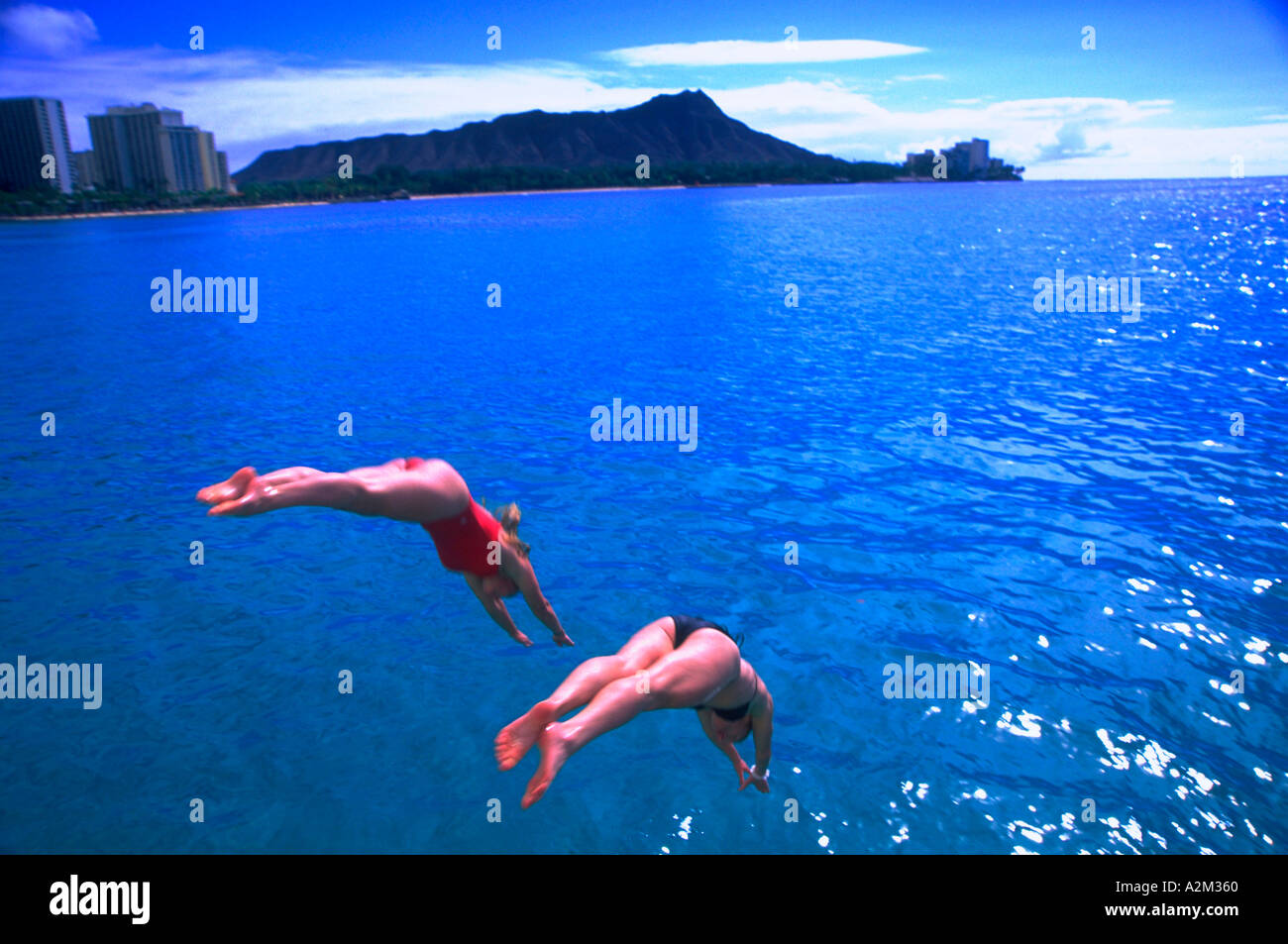 Two people diving into the crystal blue water off Waikiki Hawaii - Stock Image
