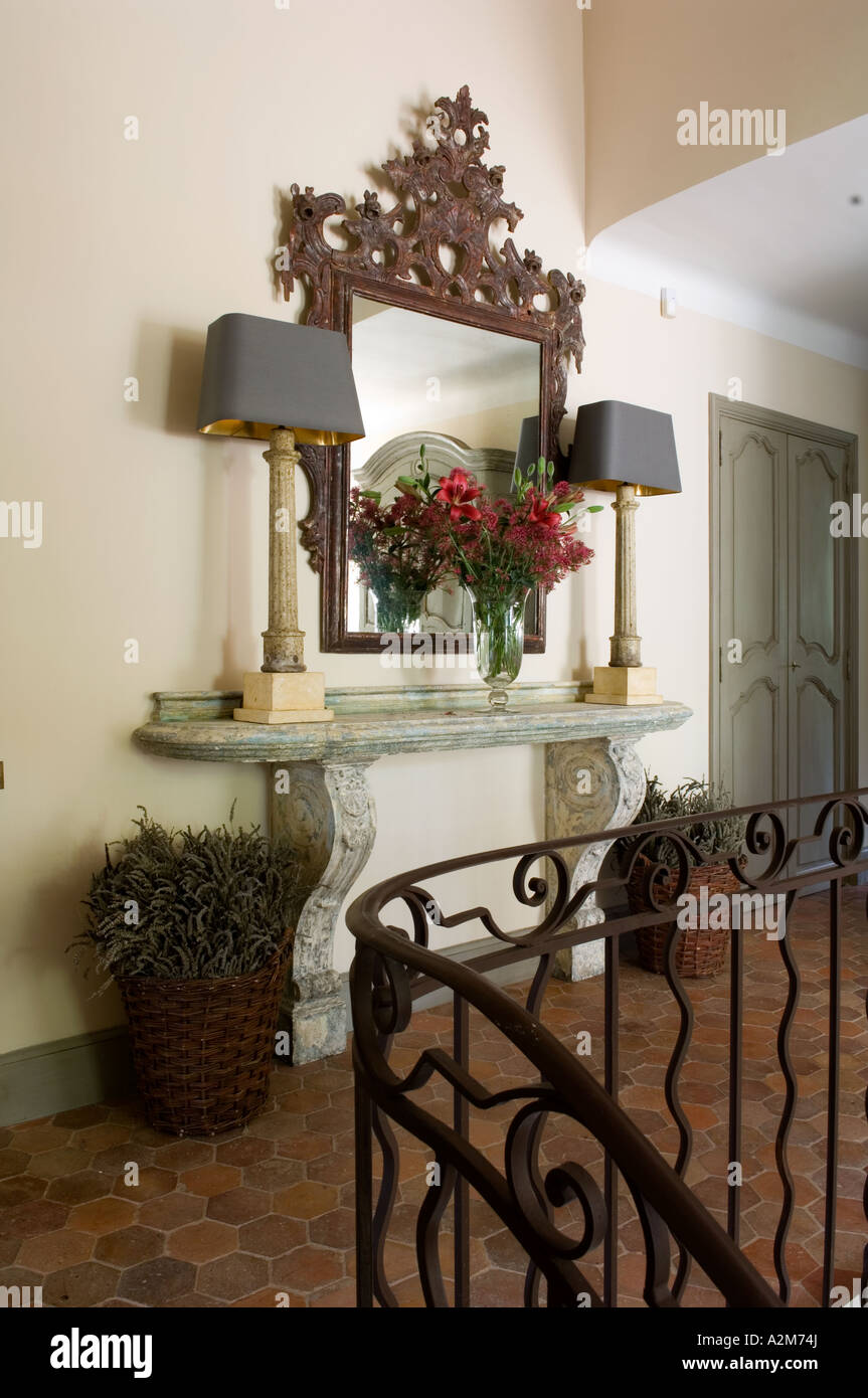 Matching lamps on hallway marble table below mirror Stock Photo