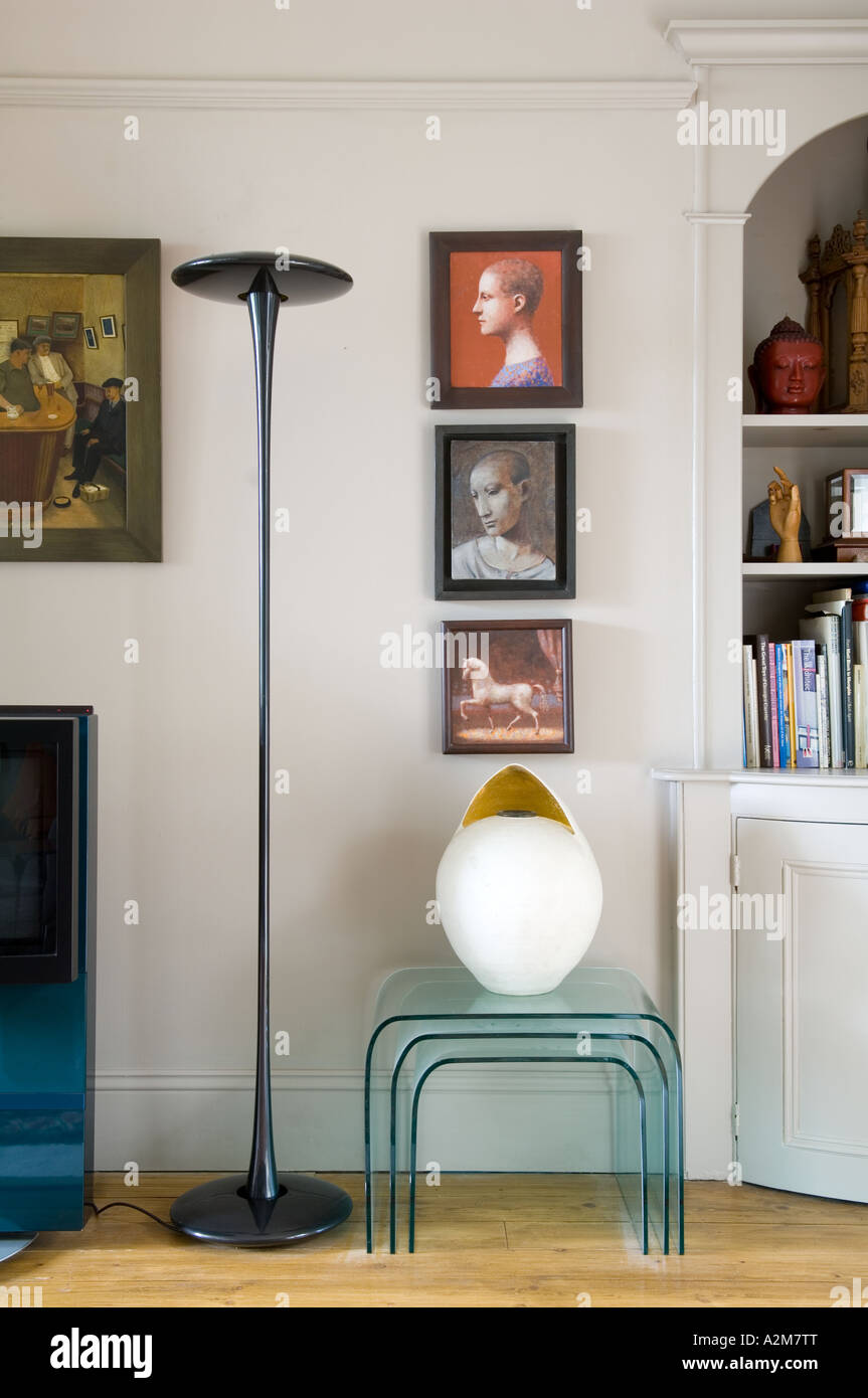 Nest of glass tables in living room with standard lamp, recessed shelving and artwork - Stock Image