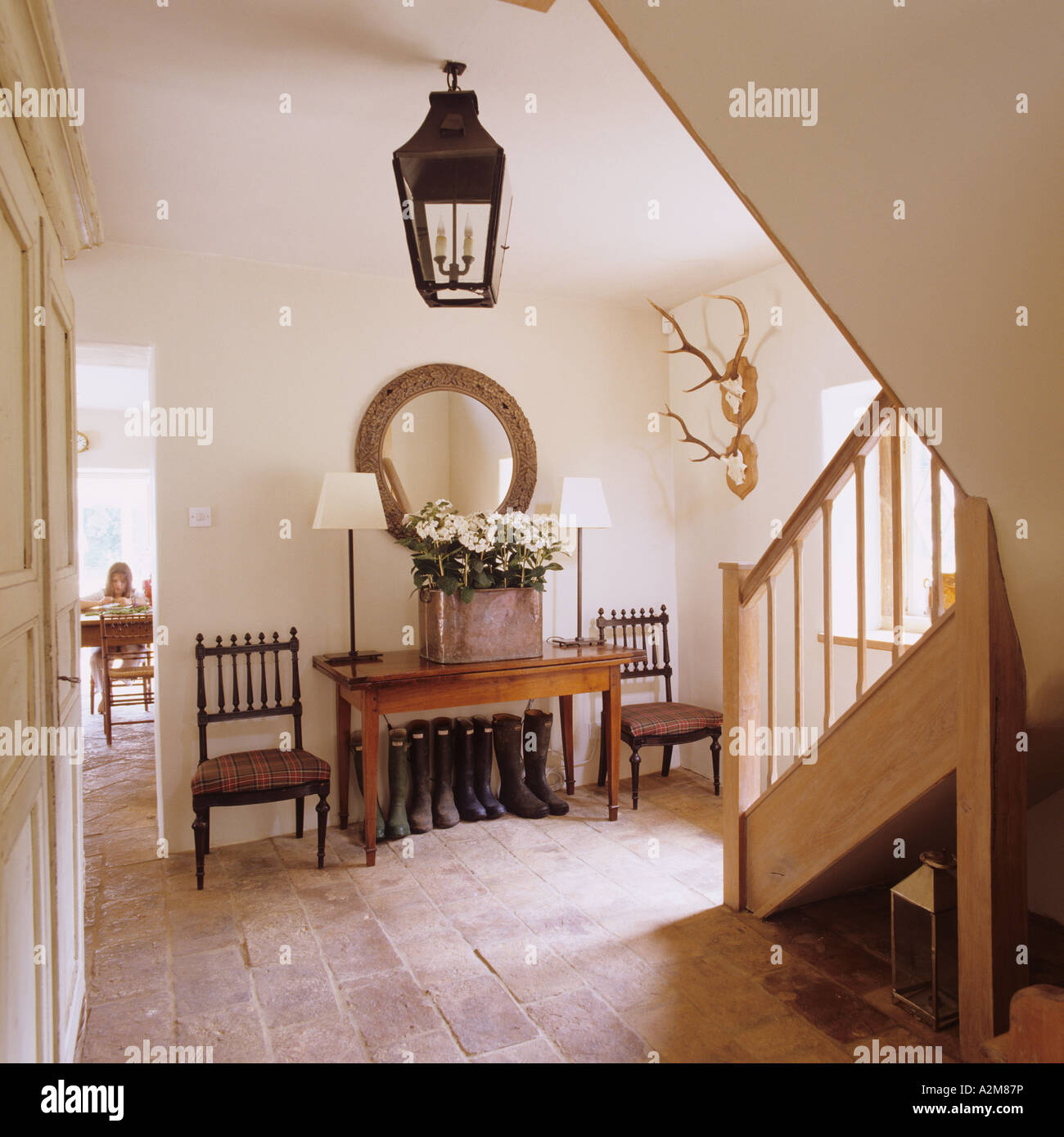 Hall with staircase and console table in converted Victorian Gloucestershire cottage - Stock Image