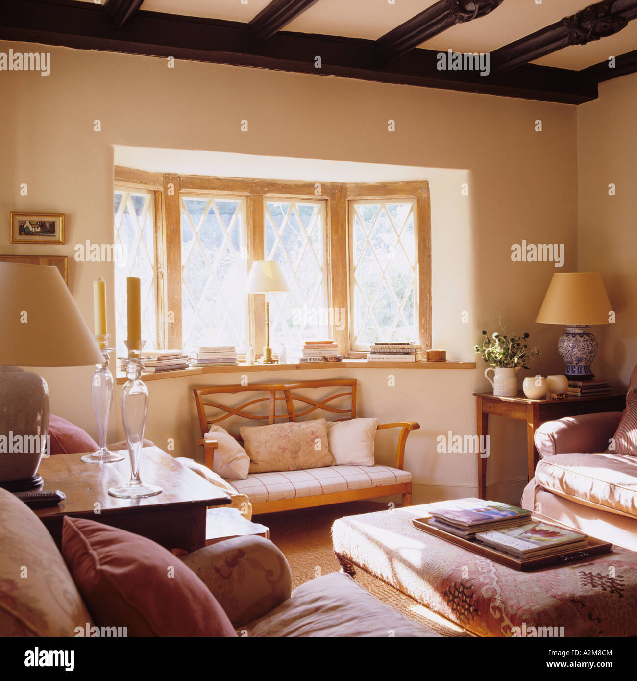 Cosy sitting room with bay window and beamed ceiling in converted Victorian Gloucestershire cottage - Stock Image