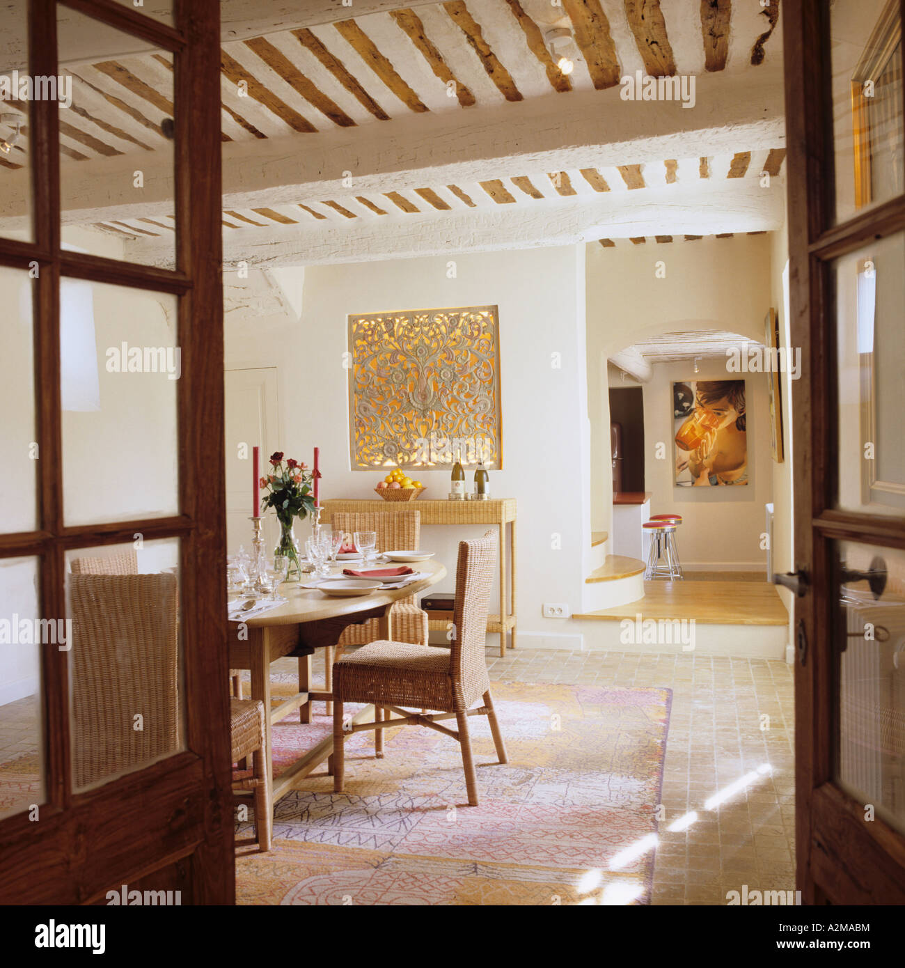 View through double doors to dining room with beamed ceiling Stock Photo
