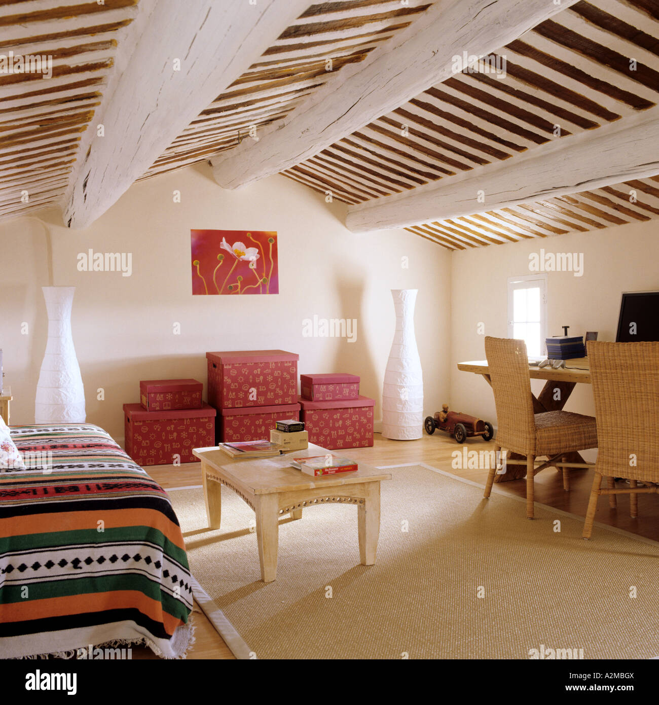 bedroom with beamed ceiling and red storage boxes Stock ...