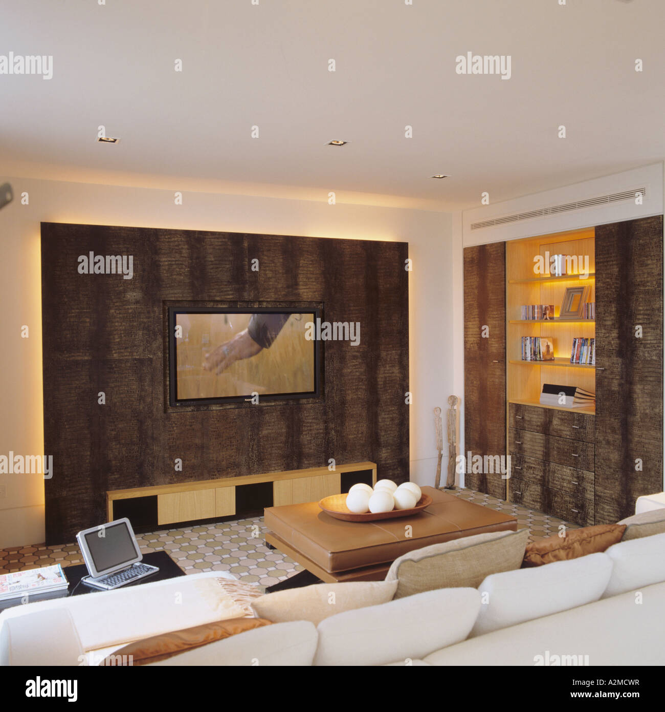 Living room with flat screen and gold recessed shelving in Thames penthouse apartment, London - Stock Image