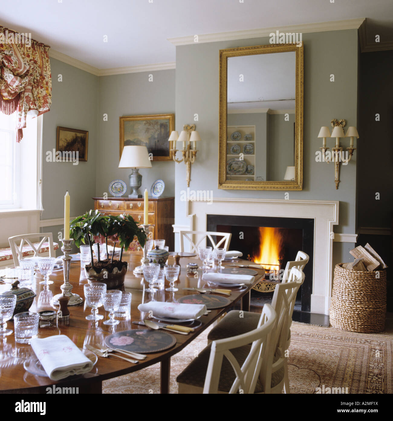 Dining Room With Laid Table And Lit Fire In English Country House