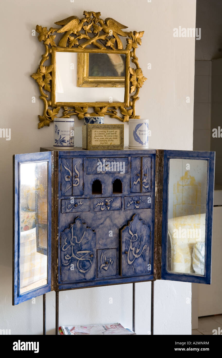 Blue cabinet with mirrored doors and Arabic lettering below gilt mirror. - Stock Image