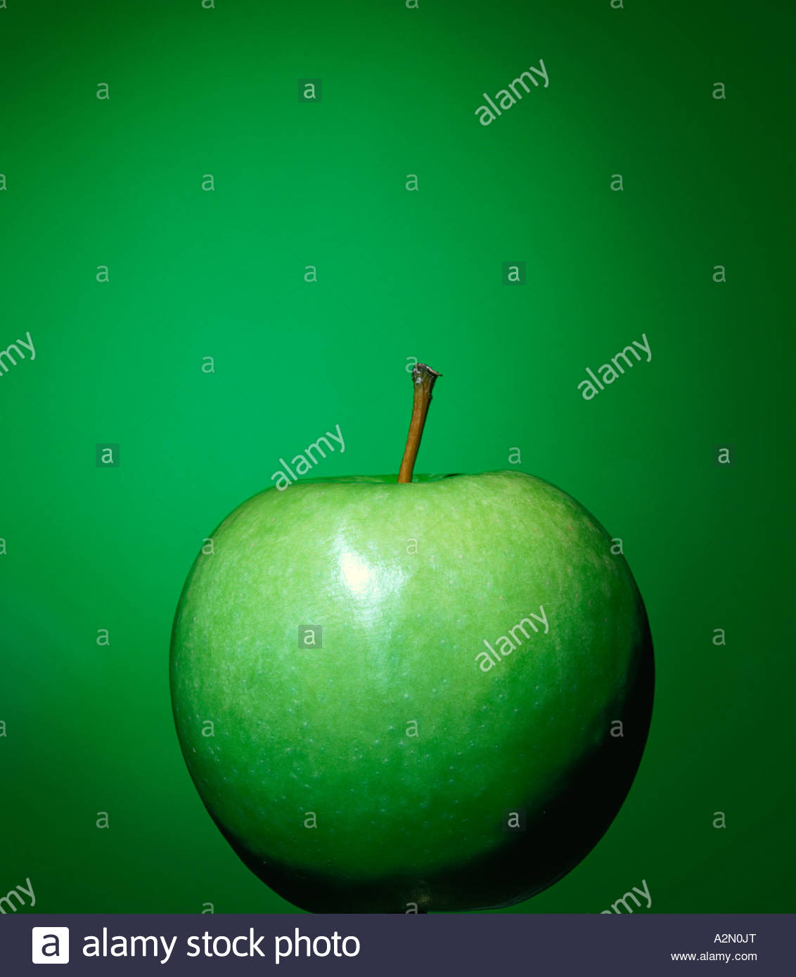 Close up of a green apple against a vivid green background. - Stock Image