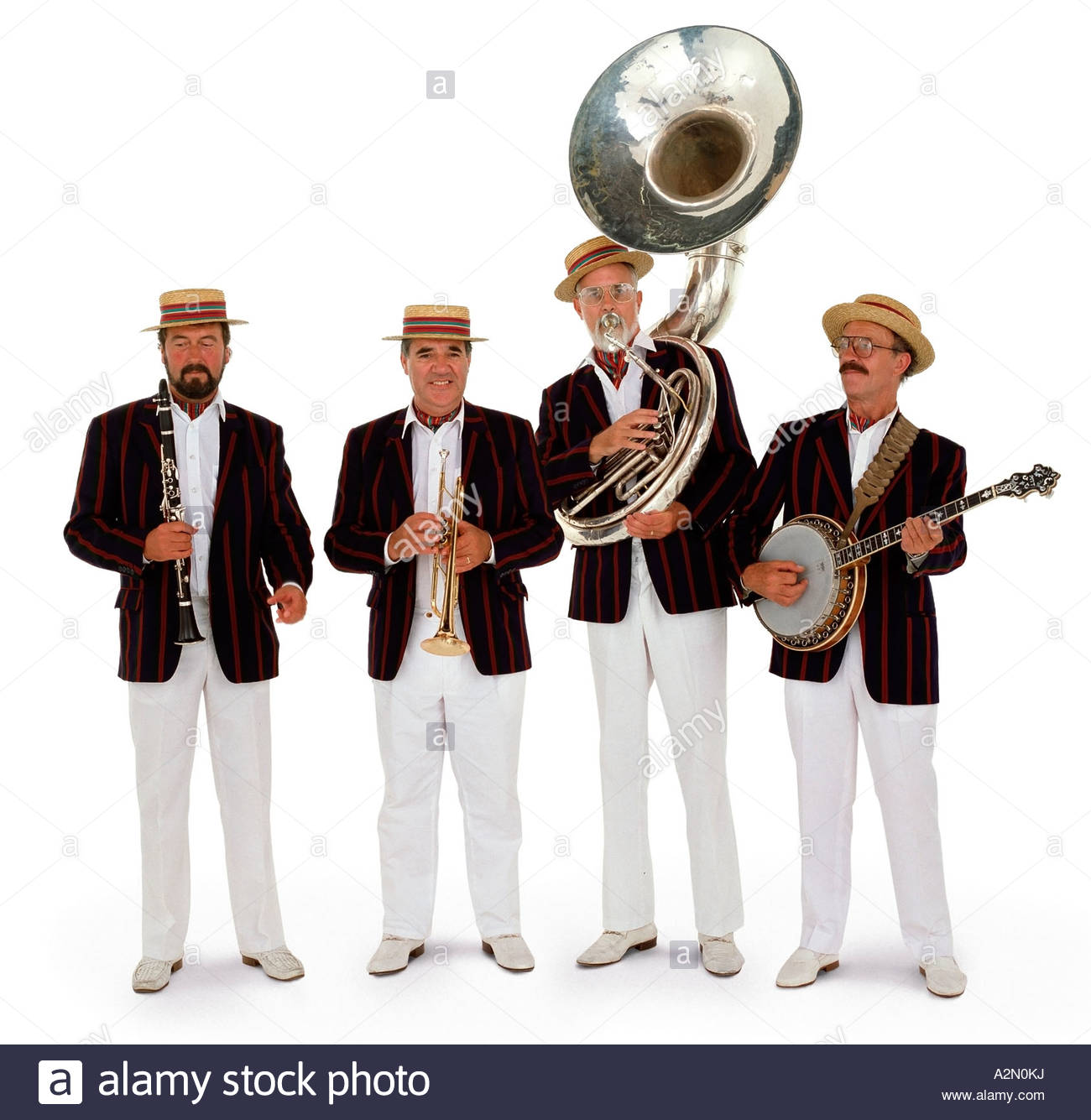 4 piece brass band wearing blazers and smart white trousers. - Stock Image