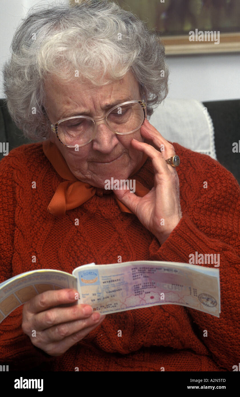 old woman looking at pension book - Stock Image