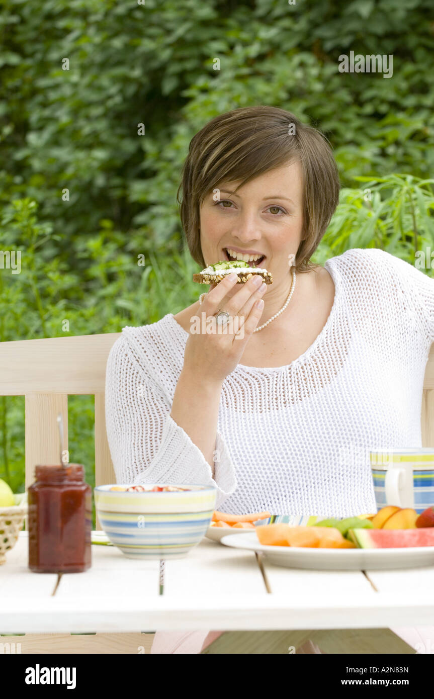 Portrait of young woman having breakfast - Stock Image