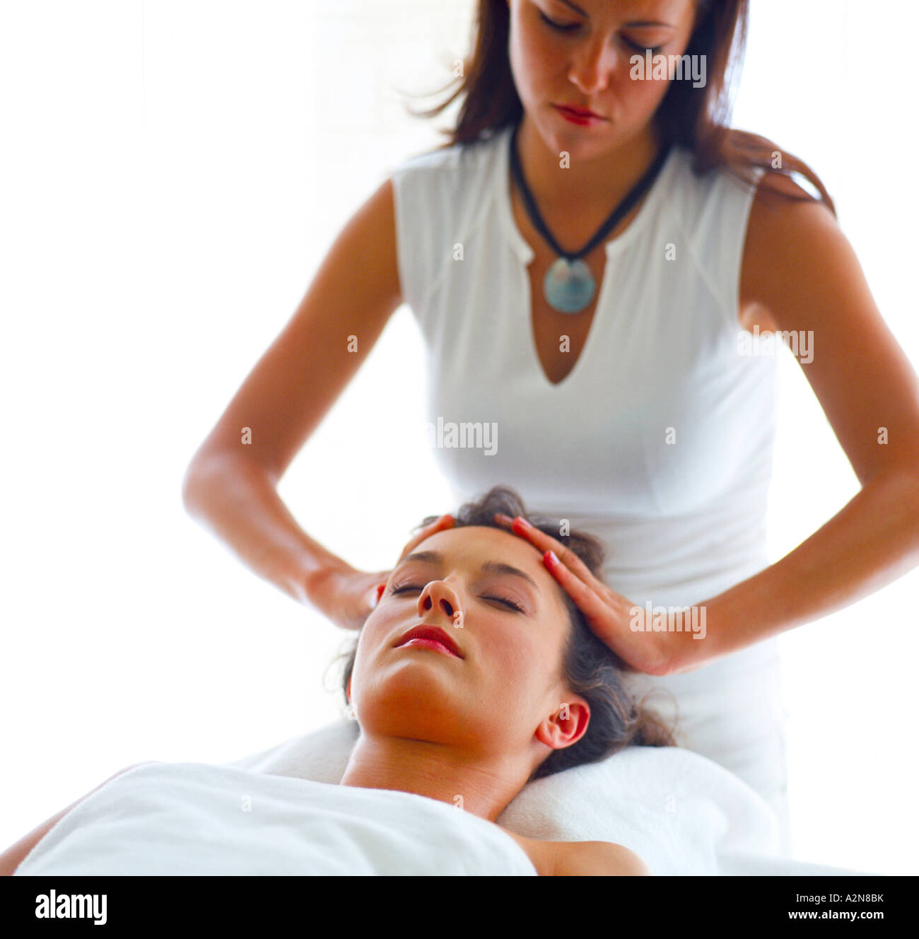 Young woman getting head massage from a therapist - Stock Image