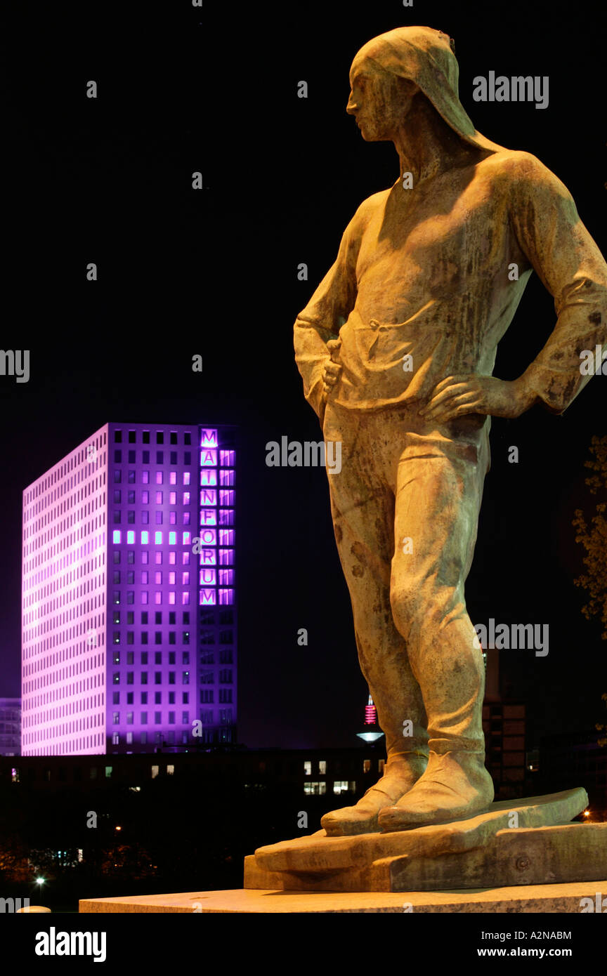 Statue of man litup at night, Mainforum, Frankfurt, Hesse, Germany - Stock Image