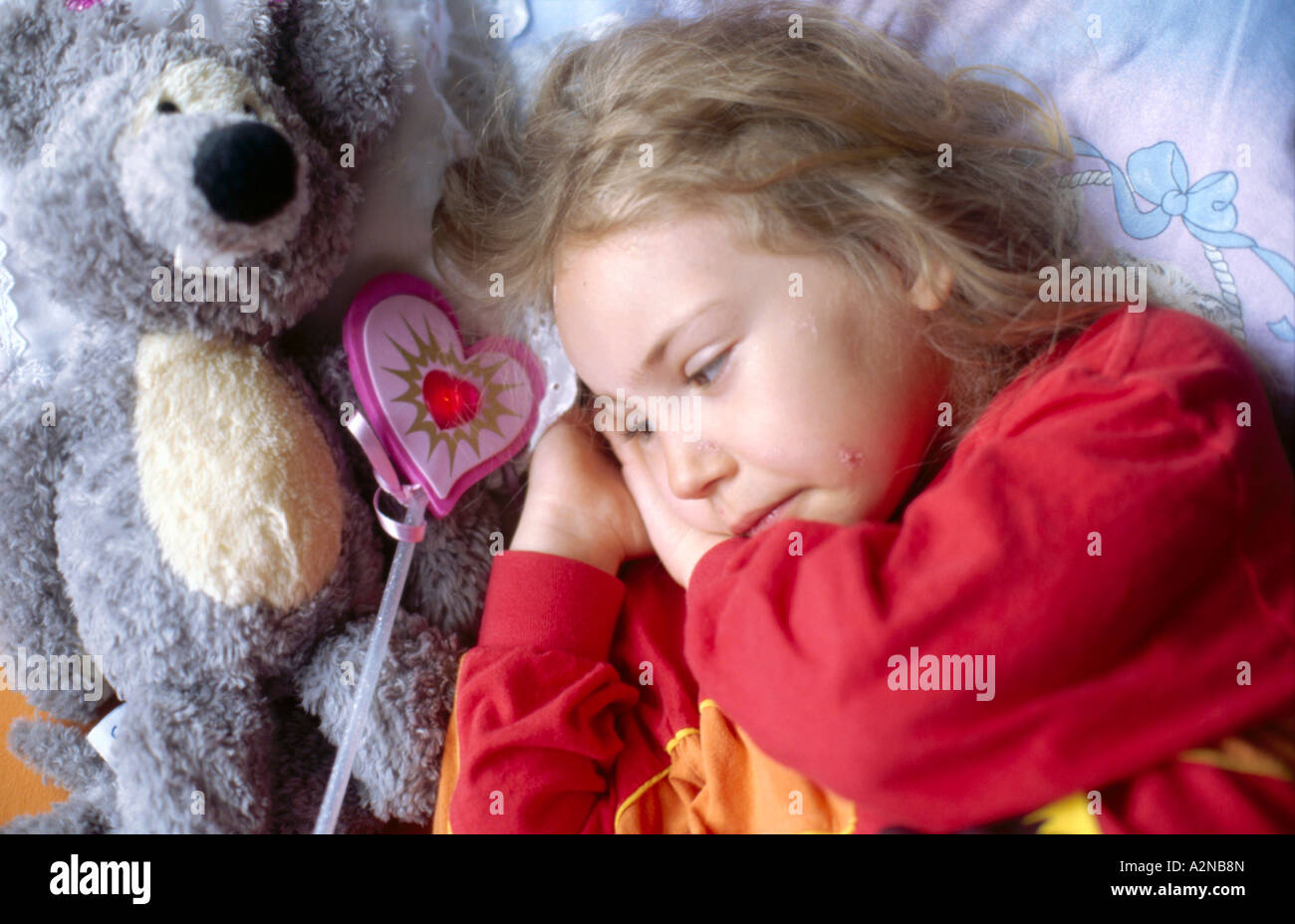 Close-up of girl lying besides teddy bear - Stock Image