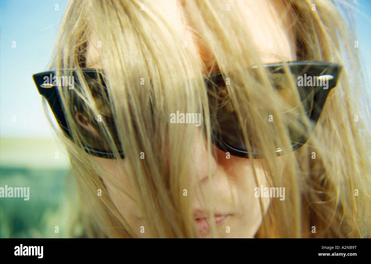 Close-up of woman with tousled hair wearing sunglasses - Stock Image