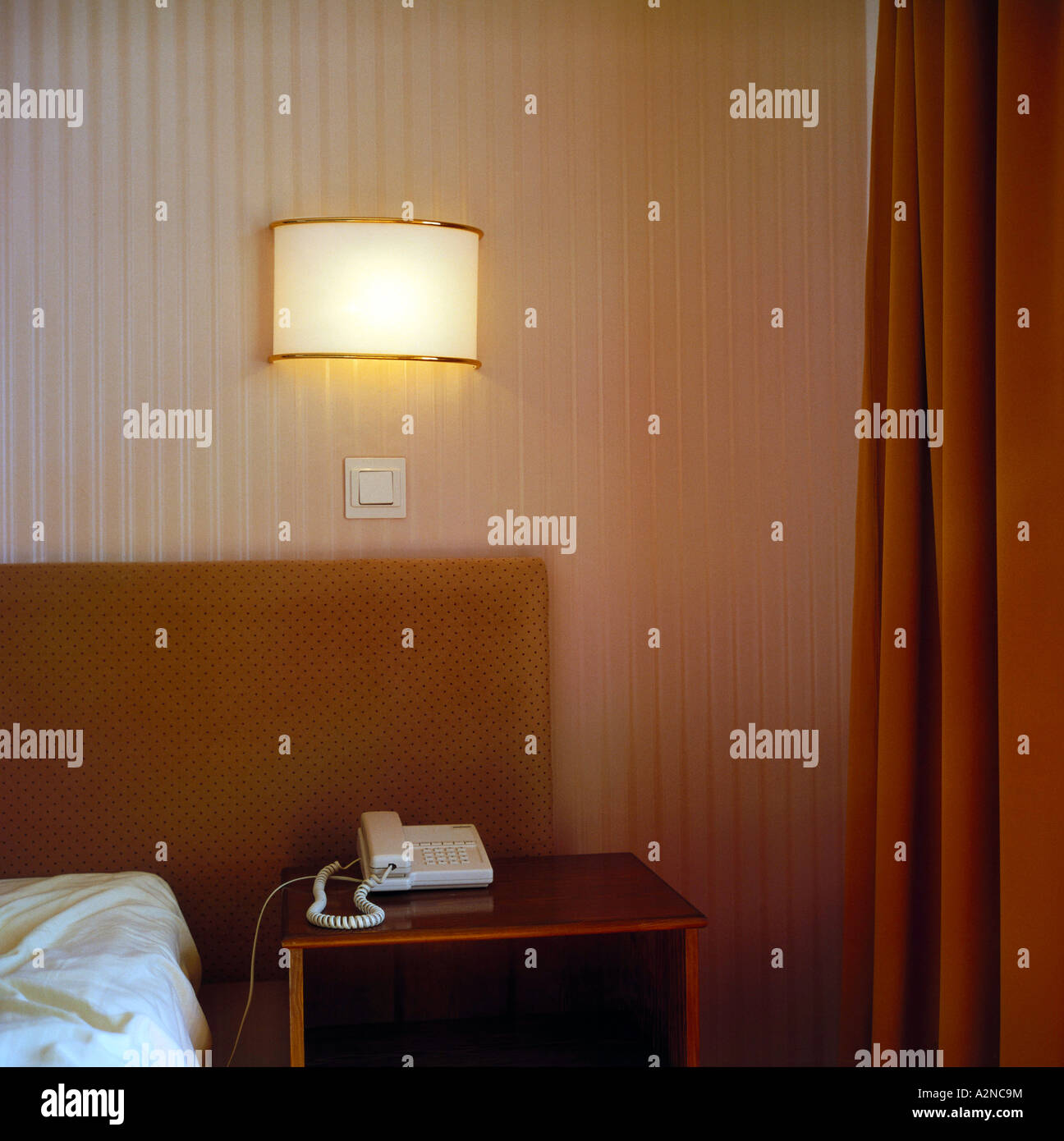 Landline phone on side table of bed - Stock Image