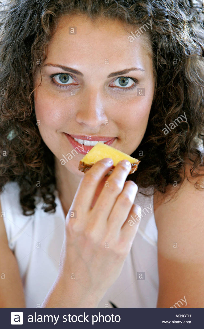 Portrait of young woman eating piece of pineapple - Stock Image
