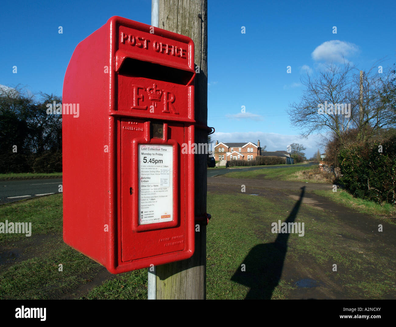 a bright red British post box fixed to a telegraph pole beside a country lane casts a long shadow - Stock Image