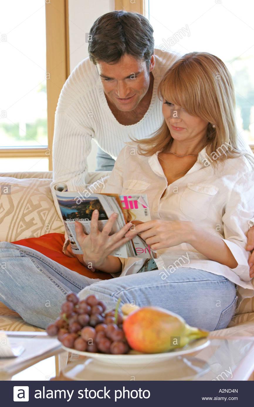 Mid adult couple reading magazine - Stock Image