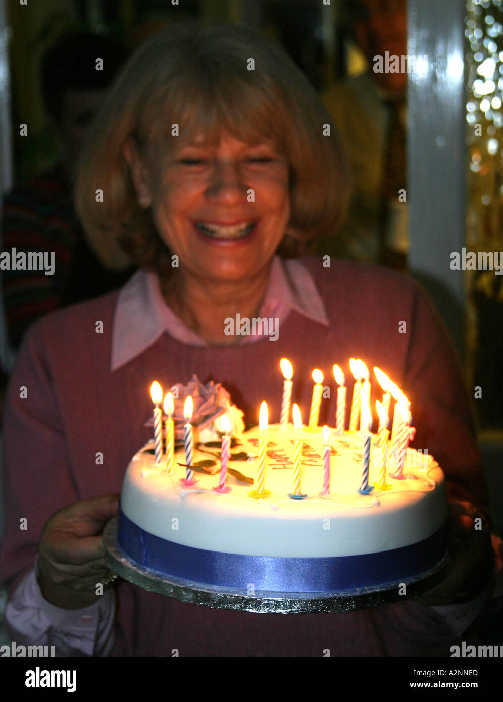 Birthday Girl Holding 60th Cake With Lighted Candles
