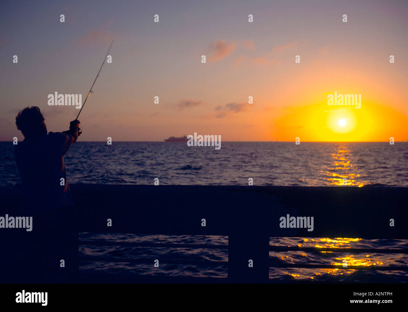A fisherman casts his line towards the setting sun at Key West Florida - Stock Image
