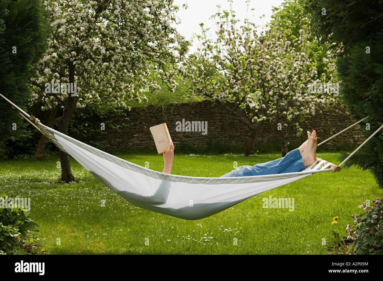 Woman in hammock reading book - Stock Image