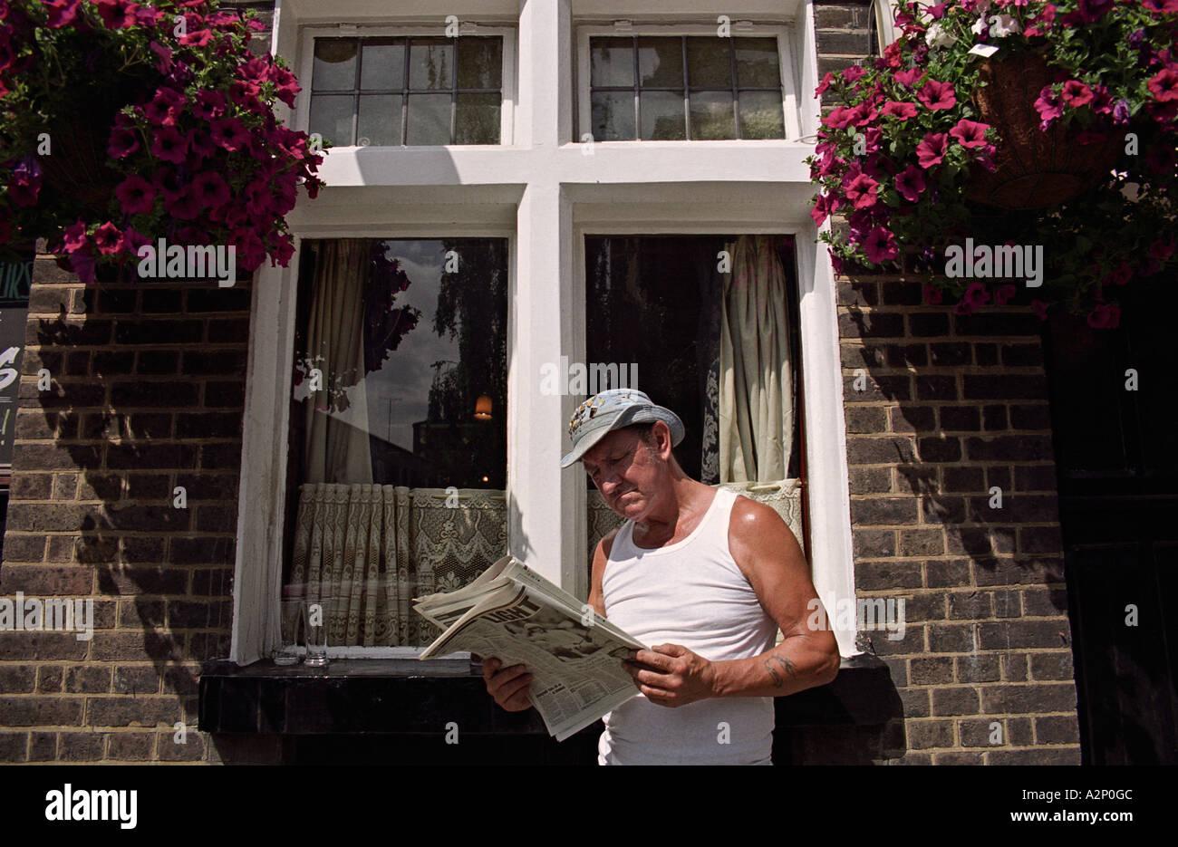 UK ENGLAND LONDON Man reading newspaper outside pub on fringe of Columbia Road flower market. Sunday lunchtime. Summer - Stock Image