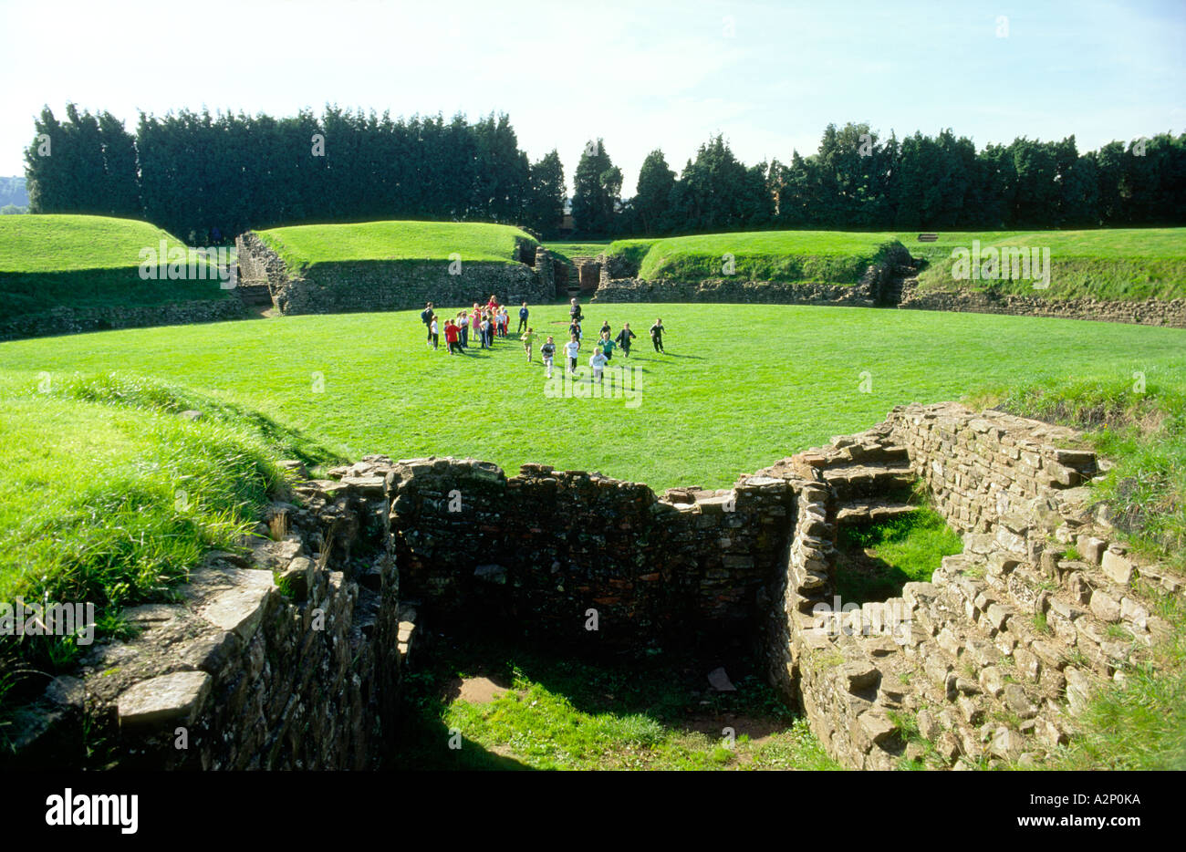 Schoolchildren inside Roman amphitheatre at Caerleon, Wales. Once headquarters of Legio II Augusta of the Roman Army in Britain - Stock Image