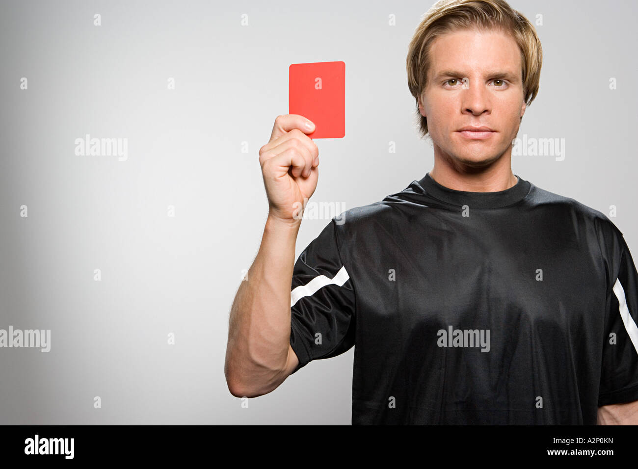 Referee holding red card - Stock Image