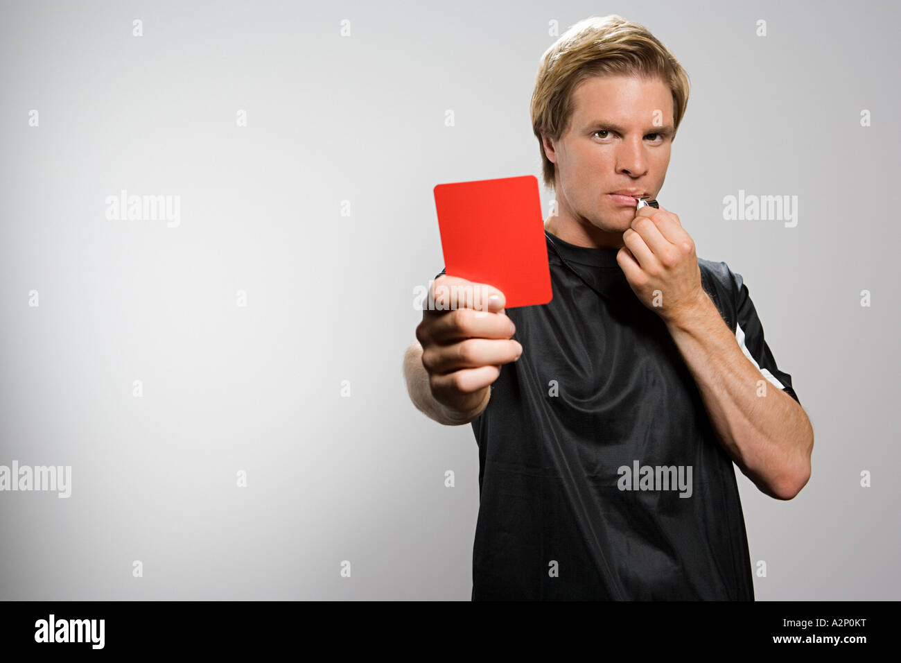 Referee holding red card and blowing whistle - Stock Image