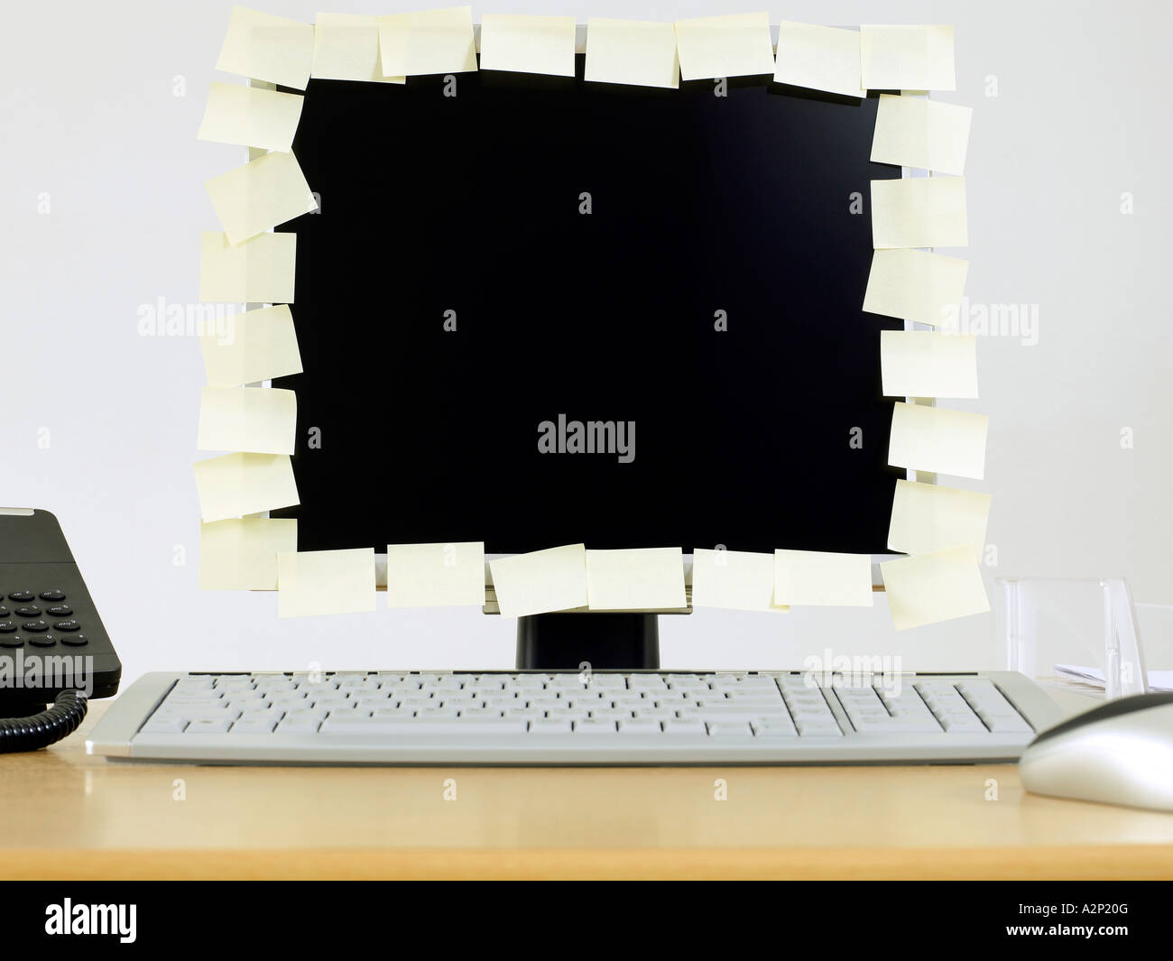 Adhesive notes covering edge of computer monitor - Stock Image
