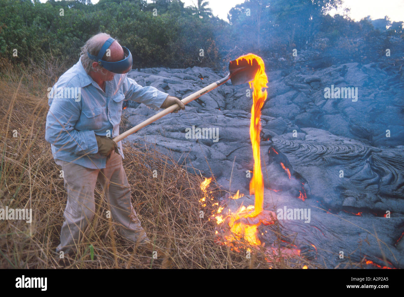 Volcanologist collecting lava sample on Big Island Hawaii  - Stock Image