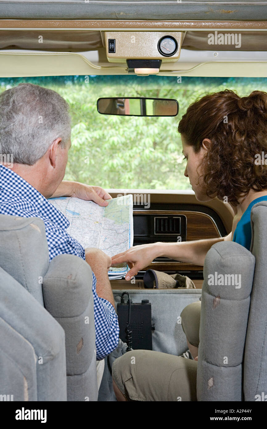 Couple planning trip with a map in caravan Stock Photo