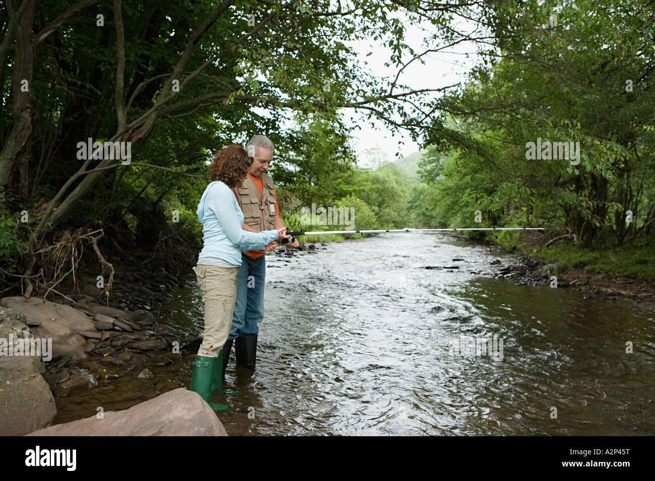 Mature couple fishing in stream Stock Photo
