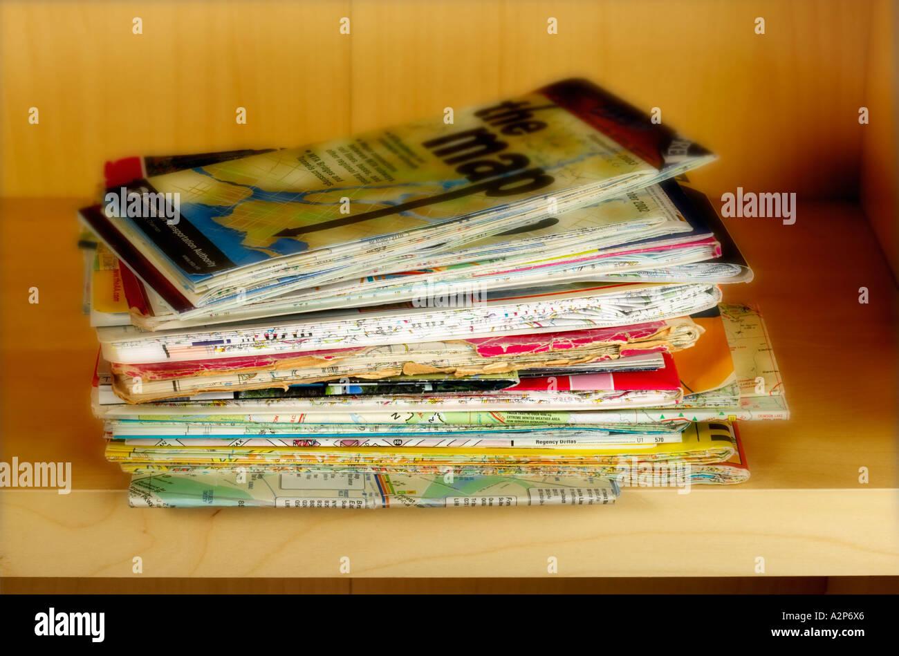 stack pile of travel maps on shelf - Stock Image