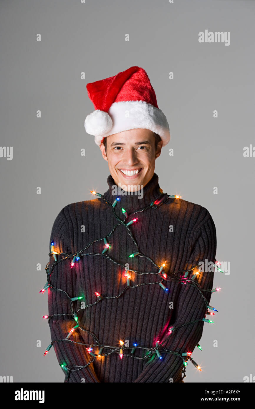 Man tied up in christmas lights - Stock Image