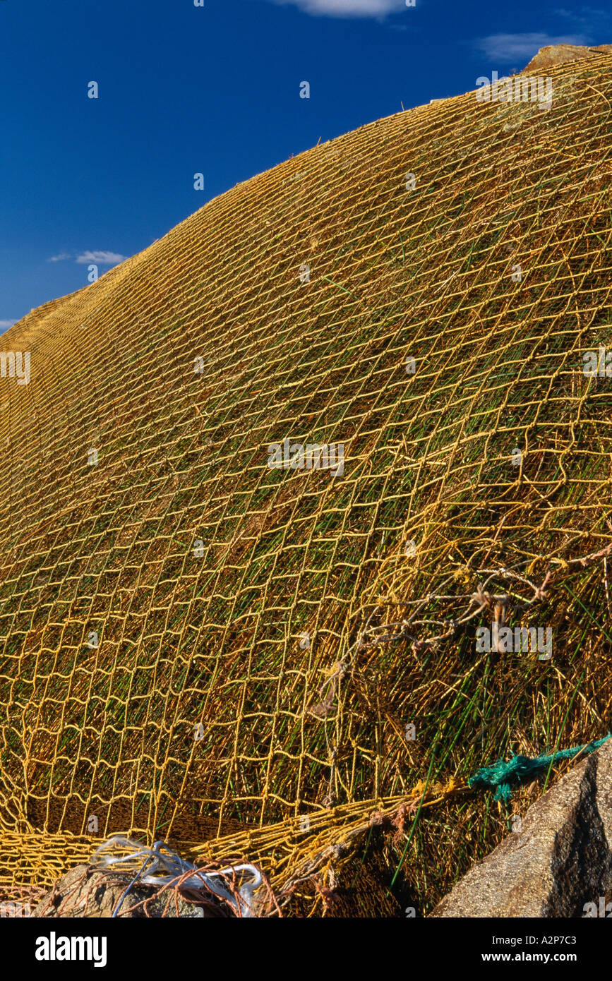 gold colored  straw and netting holding a rick of peat/turf on the irish landscape, Stock Photo