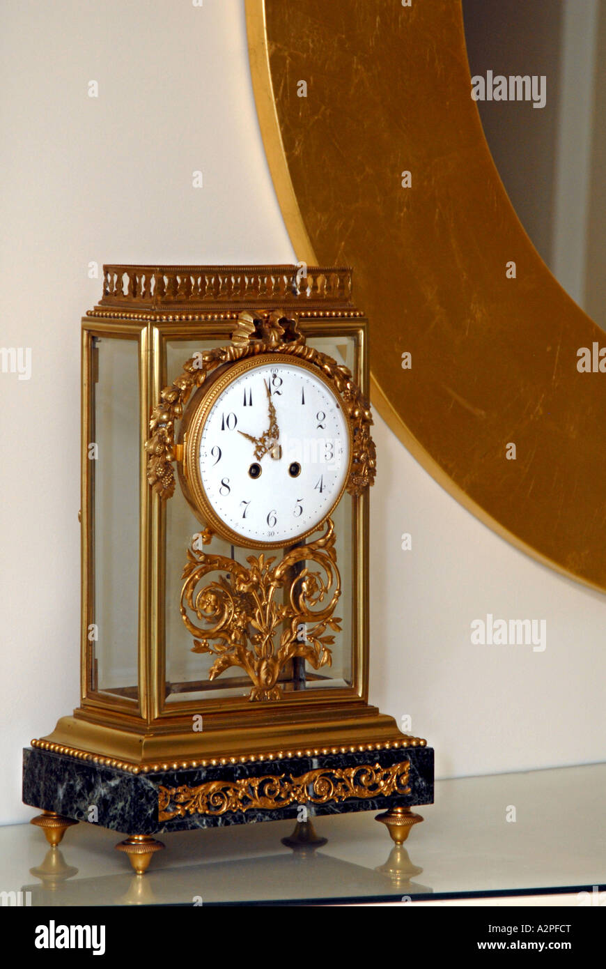 Antique 1890 s French Regulator clock on shelf gold bordered mirror in background - Stock Image