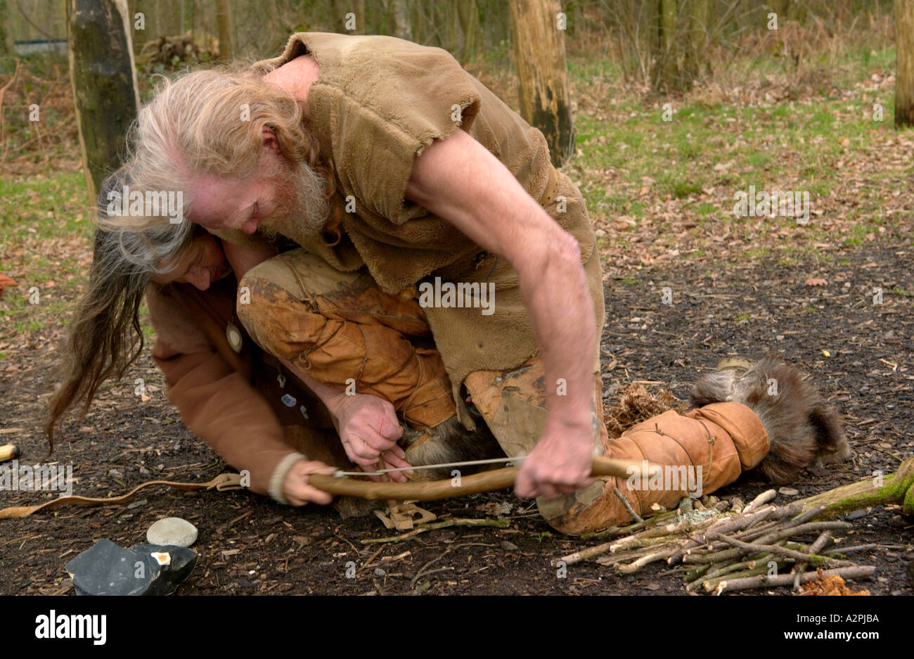 Prehistoric man & woman stone age reenactors trying to make fire at The Museum of Welsh Life St Fagans Cardiff Wales UK - Stock Image