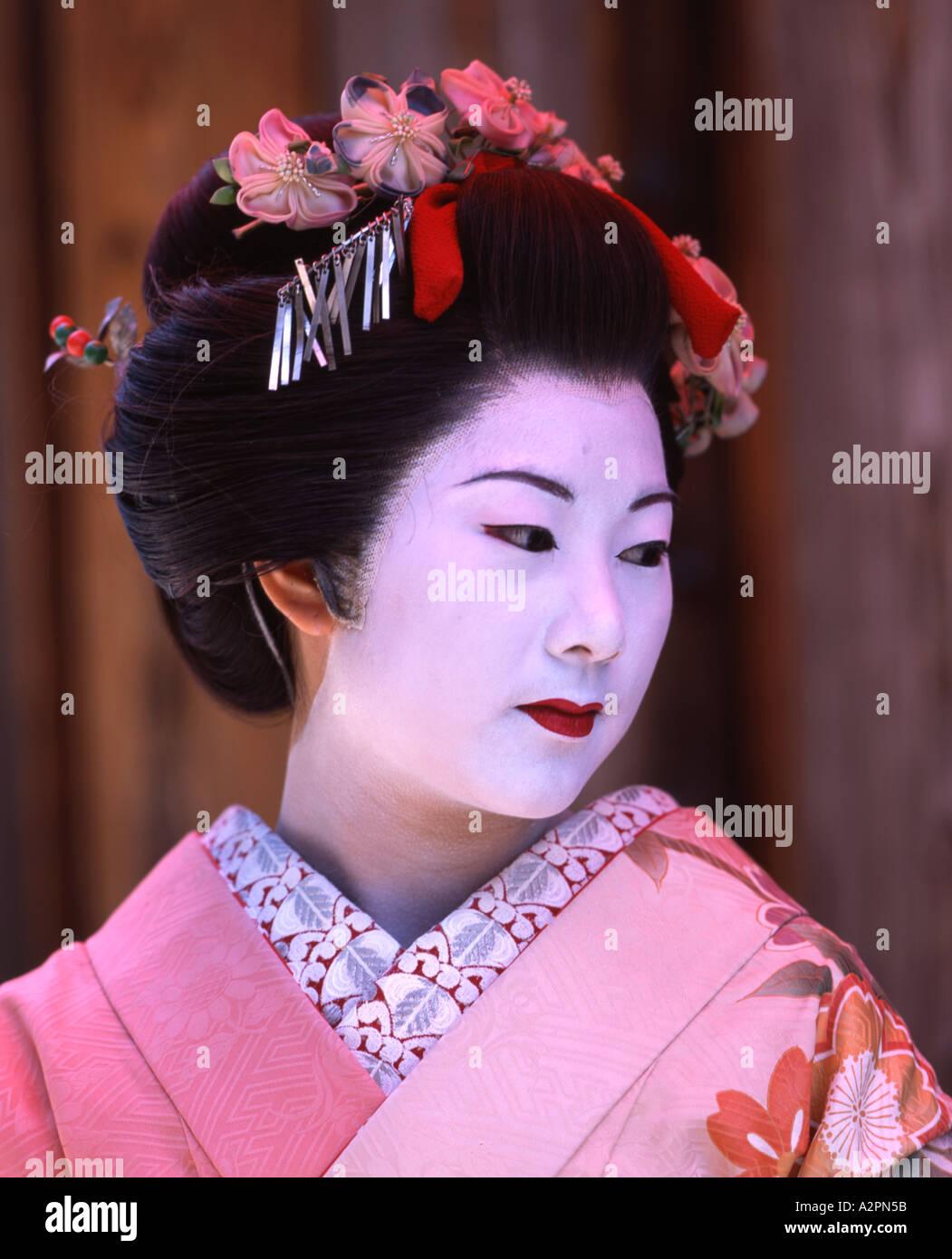 9a25a2a311 Girl in maiko trainee Geisha costume in Japanese garden of Gion Kyoto  Wearing kimono obi wig parasol makeup lipstick